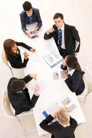 Above view of friendly team discussing documents and planning work at meeting photo