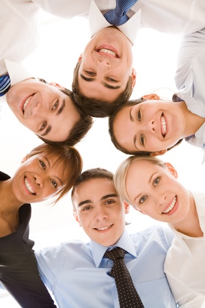 Below view of happy businesspeople making circle against white background  photo
