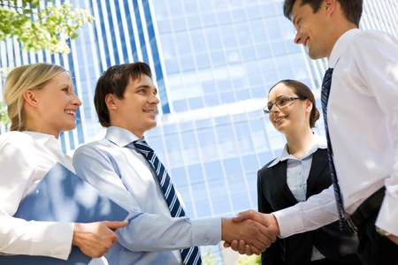 Photo of successful partners handshaking after striking deal at meeting photo