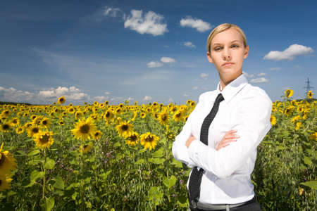 Portrait of serious business lady with folded arms in sunflower field photo