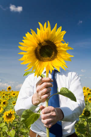 Image of man hiding face behind sunflower and giving it to you Stock Photo - 8494276