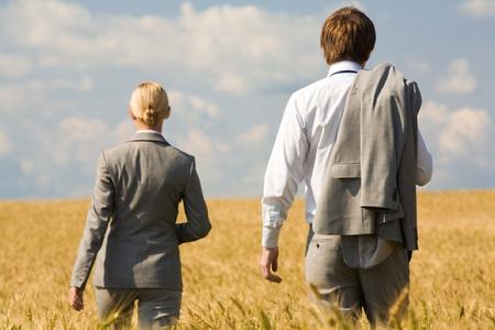 Rear view of associates in suits walking in wheat field photo