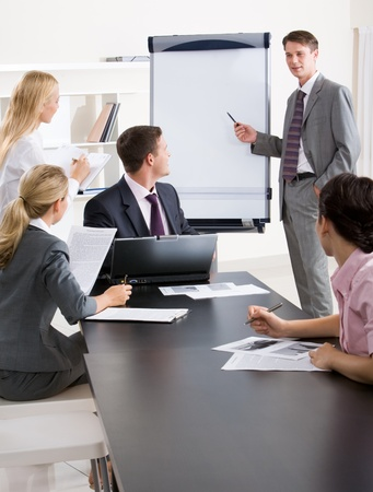 Image of confident businessman doing a presentation while their partners listening to it  Stock Photo - 8493926