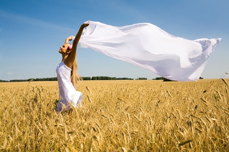 pleasures: Image of happy woman holding a white fabric in wheat meadow Stock Photo