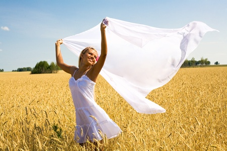 Image of happy female with white fabric in wheat meadow photo