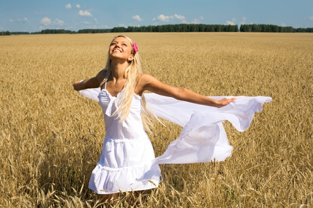 Photo of happy female with white fabric in wheat meadow photo