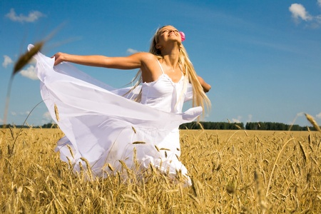 Photo of glad girl with white fabric looking upwards in wheat meadow photo