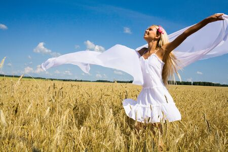 Photo of glad girl holding white chiffon shawl in wheat meadow and looking at sky Stock Photo