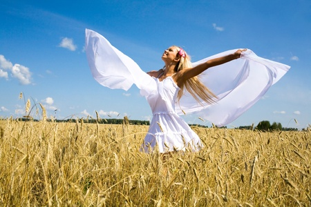 Photo of excited female with white chiffon shawl in wheat meadow and looking at sky