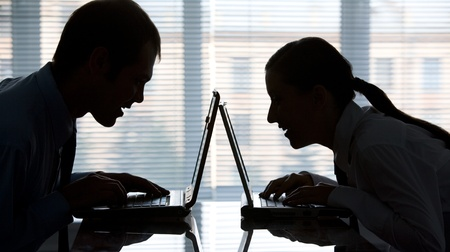 woman typing: Profiles of man and woman typing on laptops in office