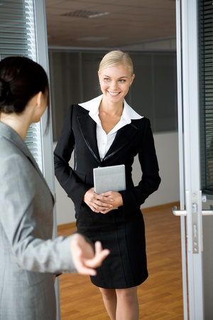 Pretty female standing by door and communicating with colleague photo