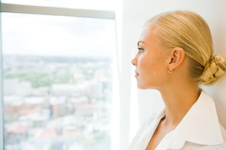 pensive: Image of pensive businesswoman looking through window in office Stock Photo