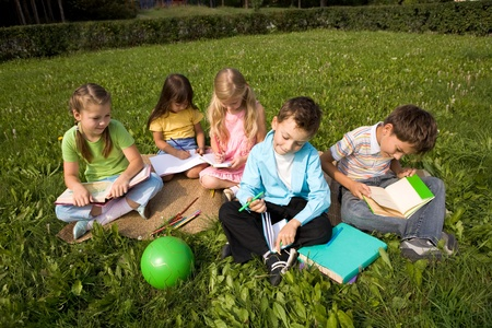 kid sitting: Portrait of cute kids reading books and drawing in park together