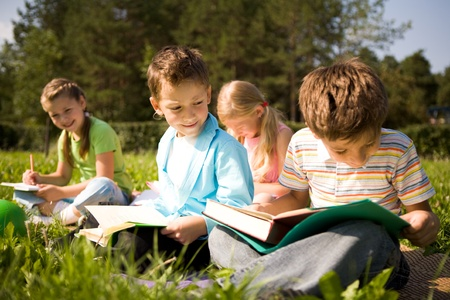 kids reading book: Portrait of cute kids reading books in natural environment together