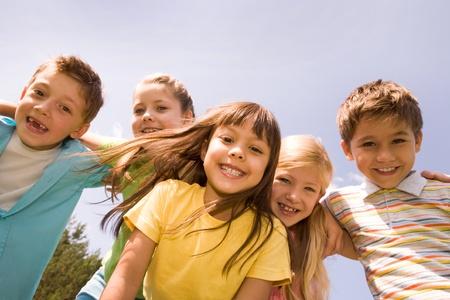 enfants qui rient: Portrait des enfants heureuses, embrassant les uns des autres et de rire avec une jolie fille devant