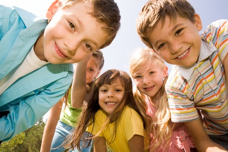 kid friendly: Photo of happy girls with handsome lads in front smiling at camera Stock Photo
