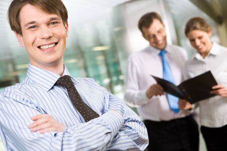 Photo of successful man looking at camera with two people interacting at the background Stock Photo - 8491988