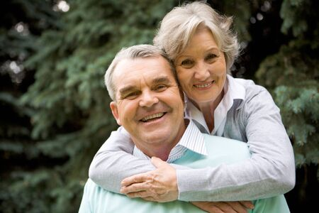 he: Portrait of senior female embracing her husband while he laughing and both looking at camera Stock Photo