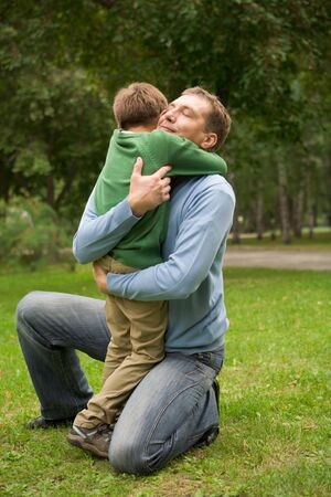 human kind: Image of happy man embracing his son in park