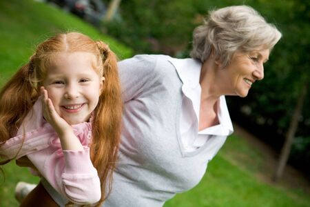 Image of happy girl spending time with her granny outside photo
