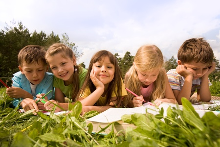 kid school: Portrait of cute kids reading books and drawing in natural environment together Stock Photo
