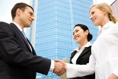 negotiation business: Image of successful partners handshaking at background of modern building Stock Photo