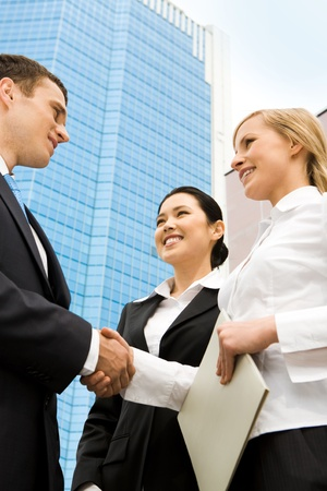 team hands: Image of successful partners handshaking after signing an agreement Stock Photo
