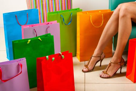 surrounded: Legs of lady sitting surrounded by colorful paper bags Stock Photo