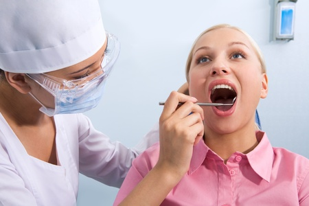 Image of young woman during inspection of oral cavity with help of mirror photo