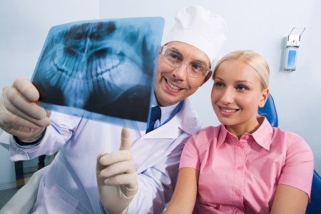 Image of young lady with dentist showing her x-ray photography photo
