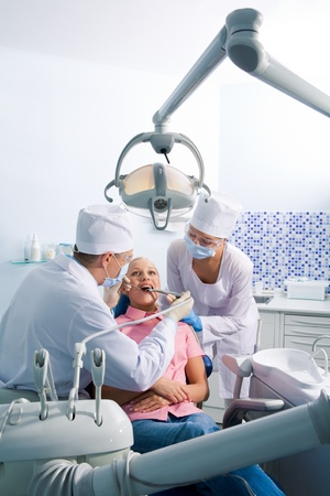 Image of young woman sitting on chair during oral sanitation surrounded by dentist and nurse Stock Photo - 8501228