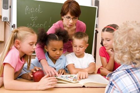 Portrait of pupils looking at open book during lesson with attention photo