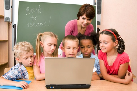 teacher: Portrait of pupils looking at the laptop display with teacher near by