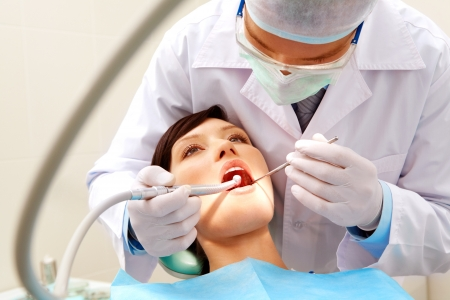 Photo of female patient with dentist over her checking up teeth and drilling them Stock Photo - 8501315