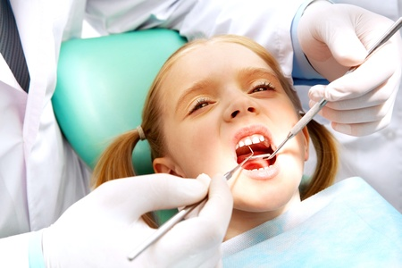 Photo of small girl with open mouth while it being examined by dentist photo