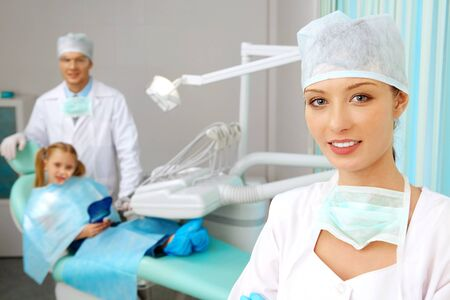 Beautiful woman in uniform looking at camera with smile on background of doctor and patient photo