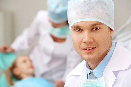 Portrait of young dentist on background of his assistant and patient photo
