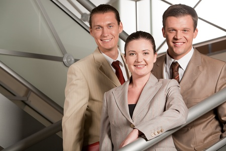 Portrait of positive business group standing on stairs of modern building photo