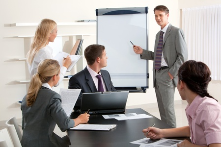 teacher teaching: Image of smart business people looking at their leader while he explaining something on whiteboard during seminar