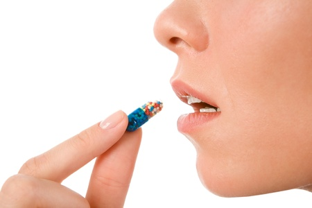 Profile of young woman holding pill by her mouth before taking it Stock Photo - 8499656