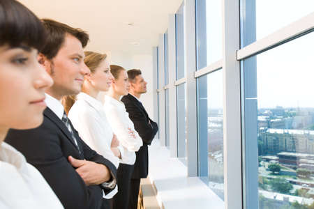 Image of business group standing in line and looking through window  photo