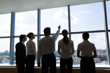 Rear view of business group standing in row and looking through window with their leader smiling at camera photo