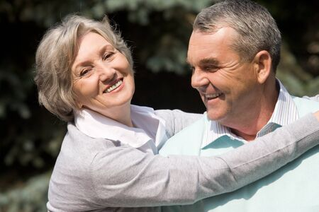 Portrait of senior female embracing her husband while he laughing  photo