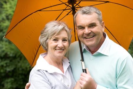 Men and women in the rain: Portrait of happy senior couple under umbrella during rain