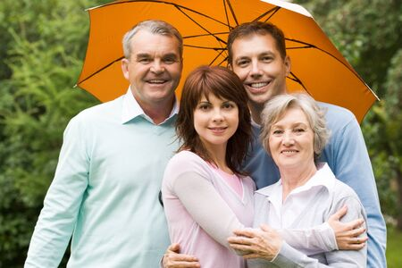 Portrait of senior and young couples under umbrella outdoors photo