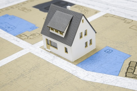 Close-up of toy house model on blueprints with its design photo