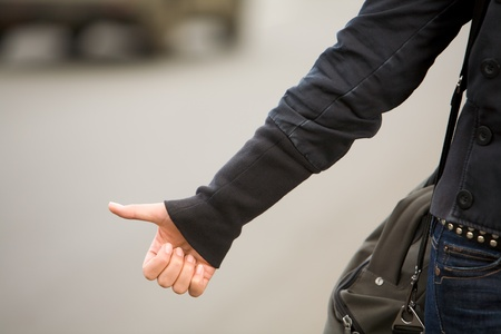 hitchhiking: Close-up of female hand gesture of hitchhiking outside Stock Photo