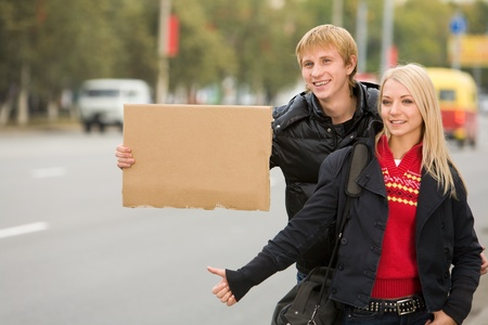 Photo of pretty girl and handsome guy hitchhiking on city road photo