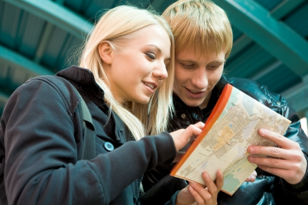Photo of pretty girl and handsome guy looking at city map outside photo