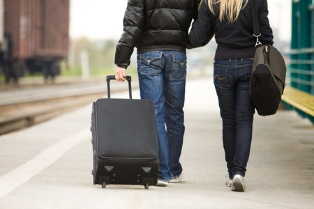 Rear view of couple walking down train station with their baggage photo